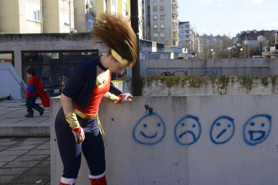 Woman dressed as Wonderwoman in the front shaking her head, so her hair is flying. On the wall beside her are 4 graffiti faces: smiley, sad, unsure and happy. Behind, a small child with the red cape is walking away. Set amongst 'brutalist' architecture.